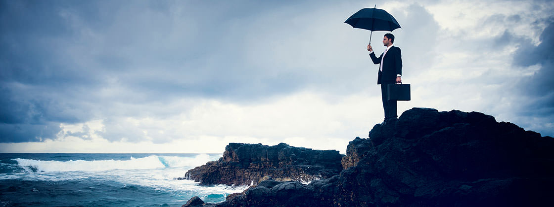 Risk management - Business man with umbrella standing on cliff at the coast