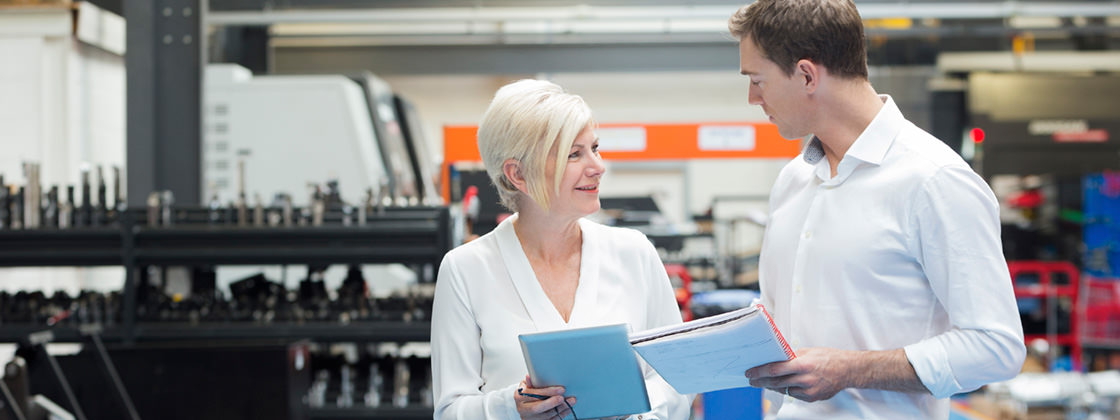 Two businesspeople discussing in factory - Purchasing with Microsoft Dynamics NAV